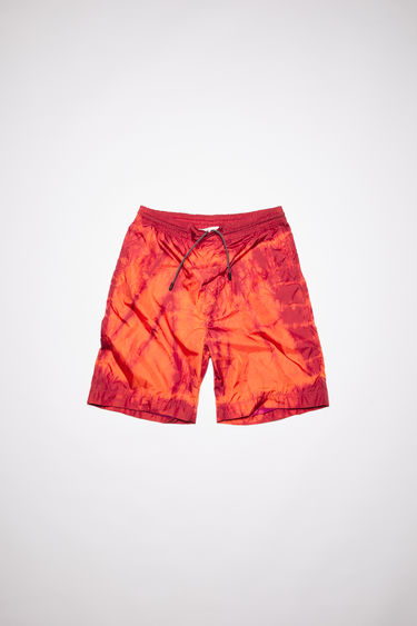 Acne Studios coral red shorts is made from tie-dyed repurposed lightweight nylon with one back patch pocket featuring a symbol print.