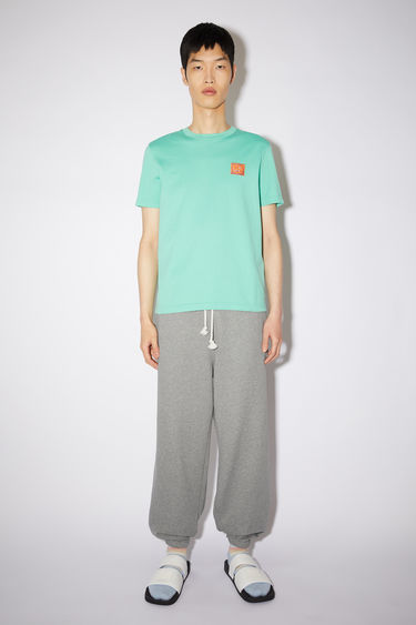 Acne Studios jade green cotton jersey t-shirt features a contrasting printed beaded face patch at the chest.