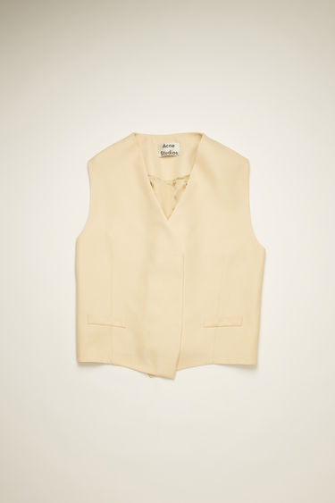 Acne Studios cream beige waist coat is crafted to an oversized fit with exaggerated arm holes and features a silver-tone metal zip closure at back.