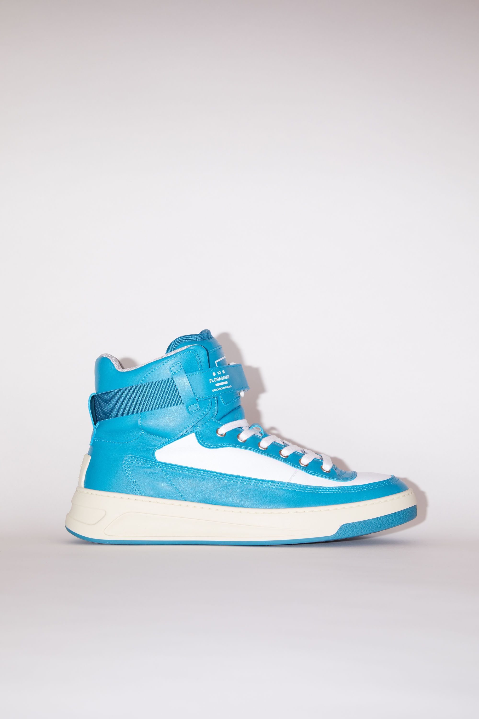 Acne Studios turquoise/white/white lace-up high top sneakers are made of calf leather with a face motif on the back sole. 001