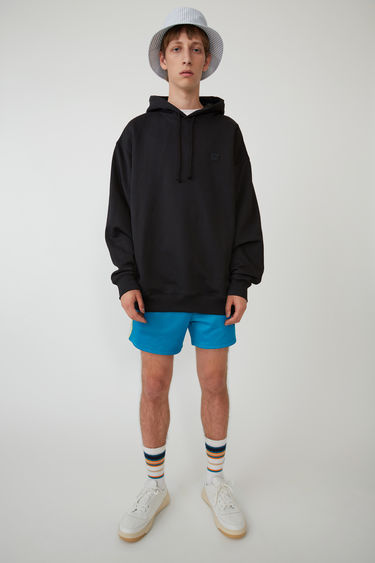 Acne Studios black hooded sweatshirt is crafted from midweight loopback jersey to an oversized fit and accented with a tonal face-embroidered patch on the chest.