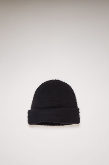 Acne Studios black beanie is knitted from soft wool and cashmere-blend yarn that's brushed to create a fuzzy pilled effect then neatly finished with a turn-up brim.