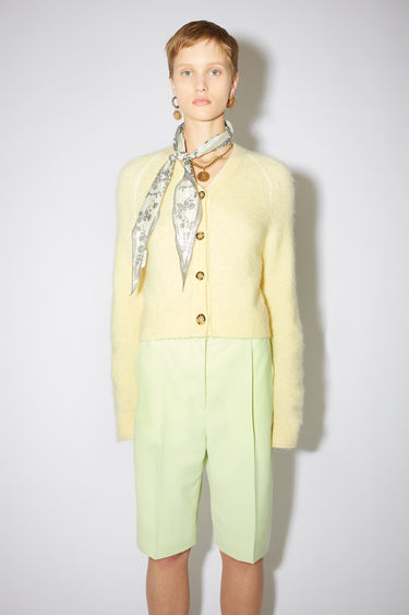 Acne Studios pale yellow v-neck cardigan sweater is made of a soft, luxurious alpaca blend with front button closures.