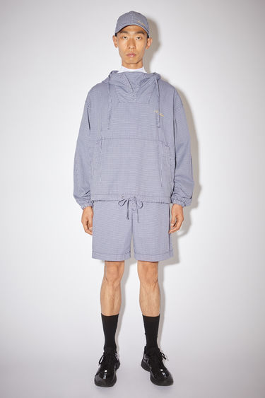Acne Studios navy/pale green hooded anorak jacket is made of a checked polyester/cotton blend with a front logo embroidery.