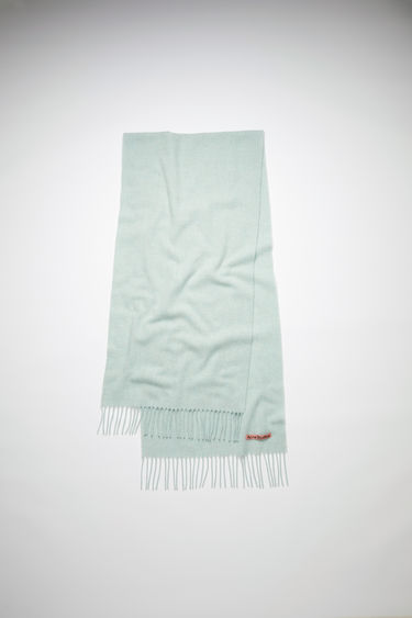 Acne Studios mint green melange narrow fringed scarf is made of pure wool, featuring a label in one corner.