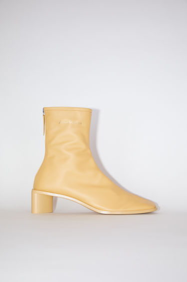 Acne Studios vanilla yellow/vanilla yellow square toe booties are made of leather with Acne Studios branding.