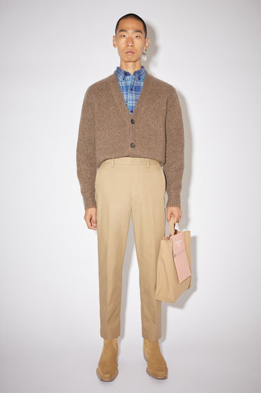 Acne Studios sand beige fitted chino trousers are made of a cotton blend.