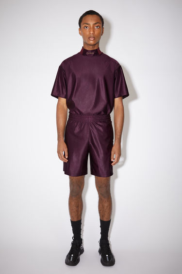 Acne Studios maroon red elastic waist shorts have piping details at the sides and a logo embroidery back pocket.