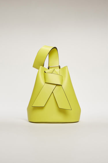Acne Studios Musubi lime green/black bucket bag features a twisted knot inspired by the formation of traditional Japanese obi sash. It's crafted from soft grain leather with a matte finish and has a detachable zip pouch to store small essentials.