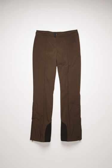 Acne Studios cacao brown trousers are cut in a straight shape with pressed creases and features a rubber pull tab on the waistband and zipped side vents.