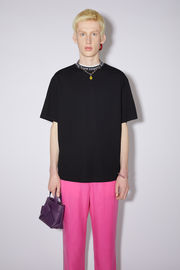 Acne Studios black t-shirt is crafted from technical interlock jersey to a relaxed silhouette with dropped sleeves and features the house logo woven along the neckline.