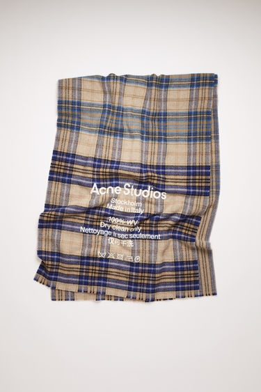 Acne Studios beige/blue scarf is crafted to a wide dimension from soft wool that's woven with tartan checks and features a large-scale logo and care instruction print on front.