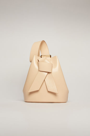 Acne Studios Musubi blush pink bucket bag features a twisted knot inspired by the formation of traditional Japanese obi sash. It's crafted from high-shine leather and has a detachable zip pouch to store small essentials.