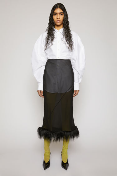Acne Studios black skirt is crafted from silk with a high-rise waist and drapes fluidly across the frame, before leading to a plush faux-fur hem.