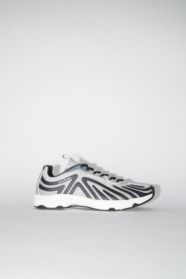 Acne Studios silver/black sneakers feature a combination of running and trail elements in one silhouette. They're crafted from semi-transparent ripstop with faux suede overlays and set on a cushioned sole.