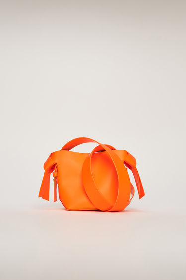 Acne Studios Musubi Micro Fluo orange bag is crafted from soft grain leather and features with a twisted knot on each side. It's finished with a short top handle and a detachable crossbody strap.