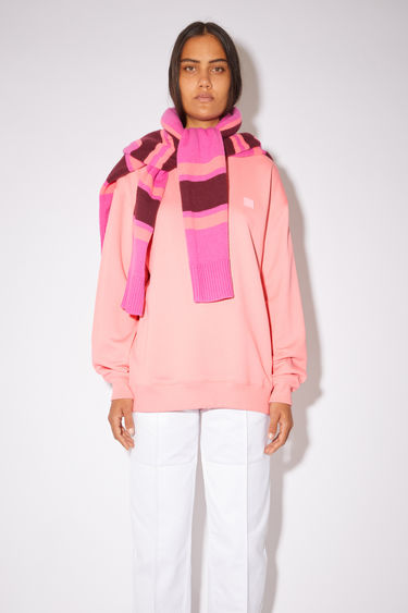 Acne Studios blush pink oversized sweatshirt is made of organic cotton with a face logo patch and ribbed details.