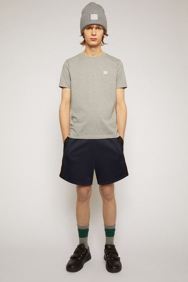 Acne Studios light grey melange crew neck t-shirt is made of organic cotton with a face logo patch and ribbed neckline.