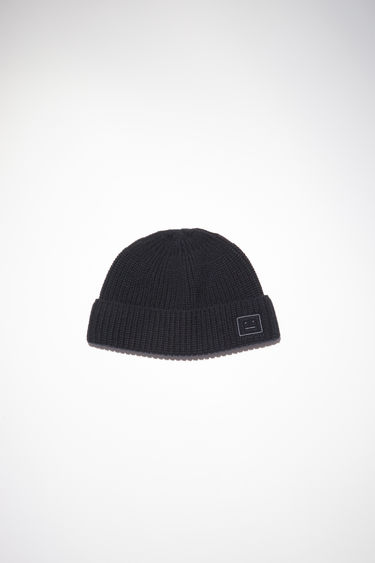 Acne Studios black fisherman beanie hat is made from rib knit wool with a face logo patch.