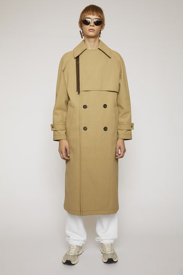 Acne Studios mushroom beige trench coat is crafted from durable cotton-canvas to an oversized fit and has a traditional double-breasted front and a storm flap.