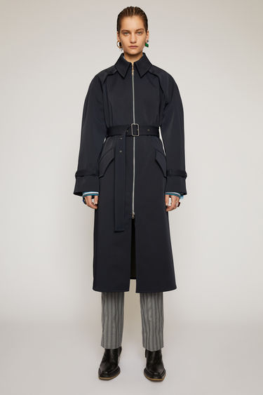 Acne Studios navy/khaki trench coat is cut to a relaxed fit from bonded technical fabric and features raglan sleeves, silver metal hardware and an exaggerated single back vent.