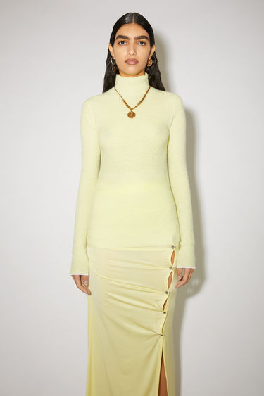 Acne Studios lemon yellow turtleneck sweater is made of a soft, ribbed knit with contrast trims at the cuffs.
