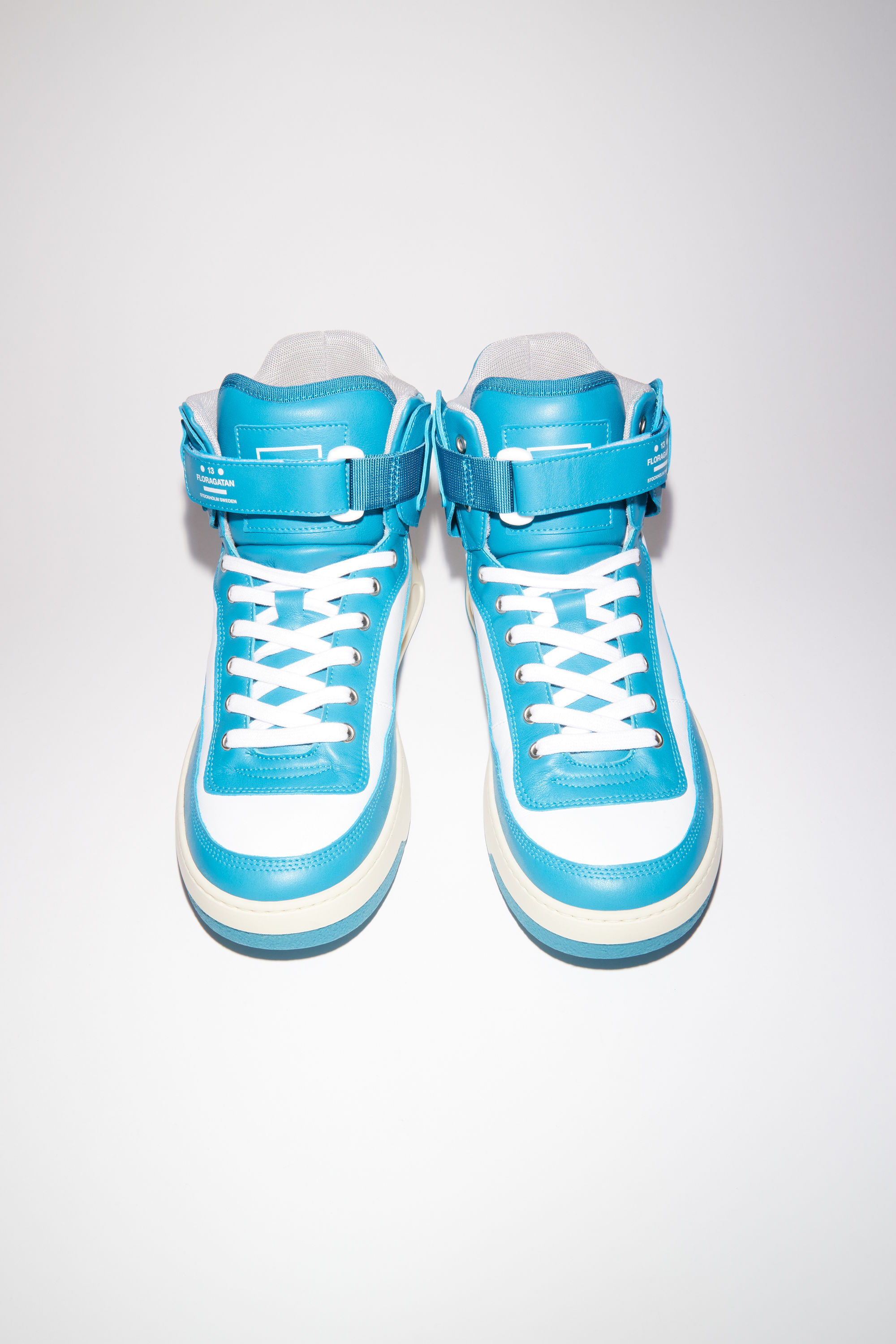 Acne Studios turquoise/white/white lace-up high top sneakers are made of calf leather with a face motif on the back sole. 002