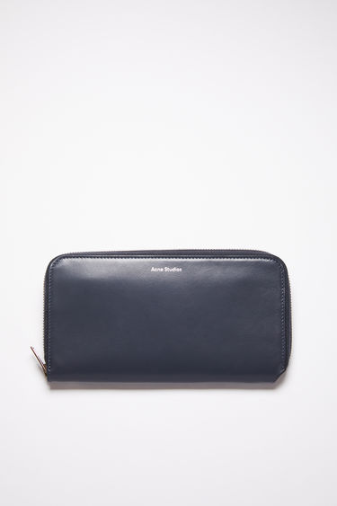 Acne Studios dark blue continental wallet is made of smooth leather with 12 card slots, two bill sleeves, and a zippered compartment for coins.