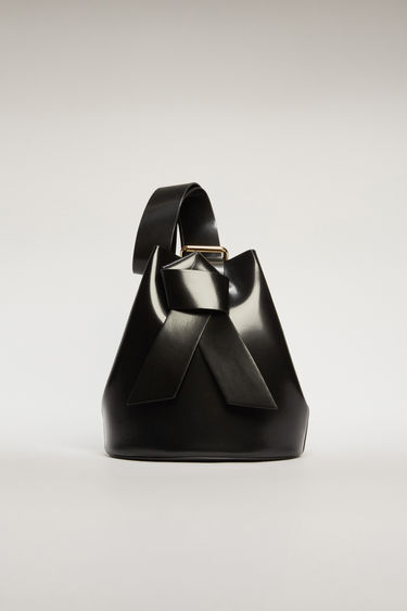 Acne Studios Musubi black bucket bag features a twisted knot inspired by the formation of traditional Japanese obi sash. It's crafted from high-shine leather and has a detachable zip pouch to store small essentials.