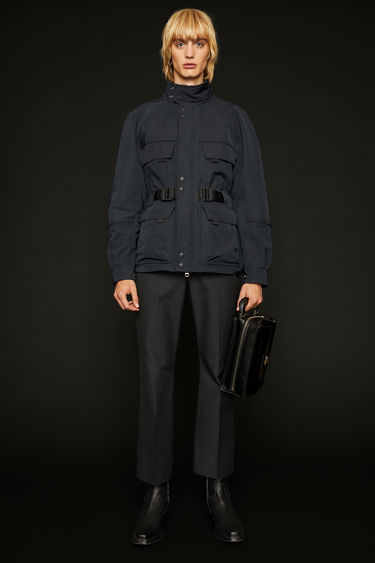 Acne Studios navy field jacket is cut from technical twill and equipped with four front pockets and a detachable webbing belt.