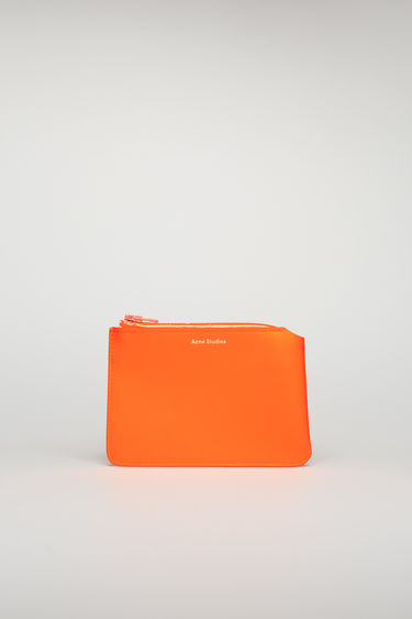 Acne Studios fluo orange zip wallet is crafted from cow leather with a matte finish and then accented with a branded zip closure.