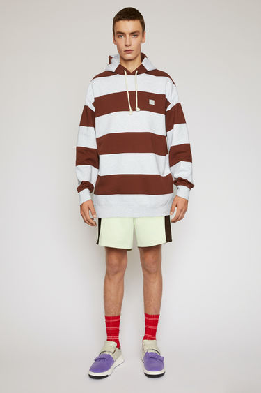 Acne Studios cognac brown hooded sweatshirt is patterned with block stripes and finished with a face-embroidered patch on the chest.