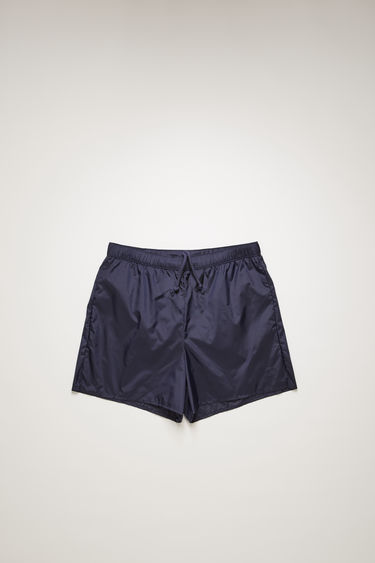 Acne Studios dark blue swim shorts are crafted from technical nylon with front and back pockets and finished with an elasticated waistband with round drawstrings.