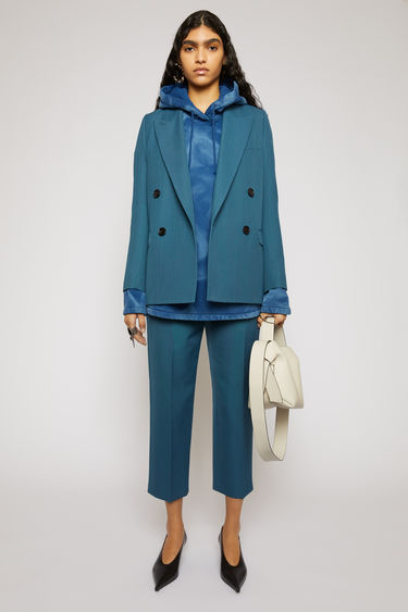 Acne Studios teal blue wool-blend trousers are tailored with a high-rise waist stitched with pleats and gradually tapers in towards the hem.