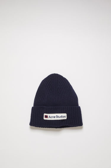 Acne Studios navy beanie is knitted in a thick rib-stitch from soft wool and features an embroidered logo patch on the turn-up.