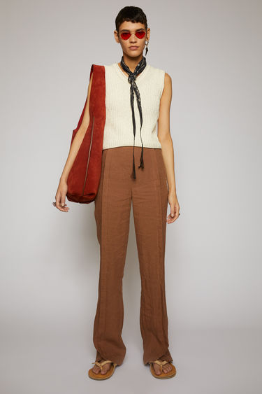 Acne Studios mink brown linen trousers are cut to flared, slim-fitting legs with a high-rise waist, then finished with stitched folds through the front.