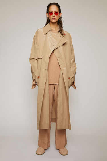 Acne Studios brown trench coat is cut to a relaxed fit from technical textured cotton that's finished with a subtle sheen. It features two-way functional patch pockets and an optional drawstring belt to cinch in the waist.