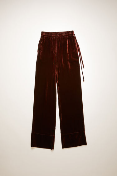 Acne Studios dark brown velvet trousers are tailored in a straight-leg shape that drapes loosely over the leg and finished with an elasticated waistband with drawstrings on the side.
