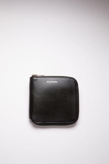 Acne Studios black medium-sized leather wallet has compartments for cards, coins, and documents.