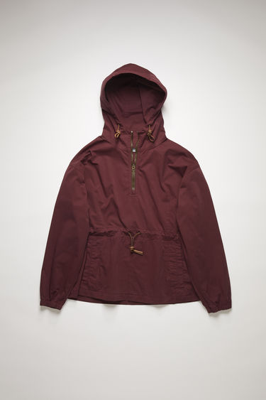 Acne Studios burgundy half-zip jacket is crafted from soft, garment-dyed cotton to an oversized silhouette and features a drawstring hood and waist that's accented with leather cords.