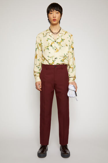 Acne Studios burgundy trousers are tailored in a straight shape with a mid-rise waistband, and finished with side pockets and welt pockets at the back.