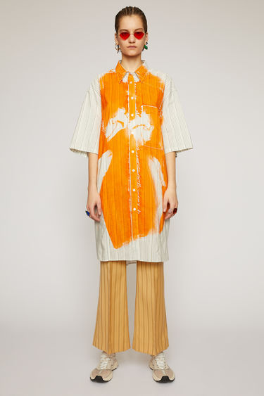 Acne Studios off white striped shirt dress is cut to an oversized fit from a lightweight cotton-blend and features a faintly printed cover of Propaganda Magazine.