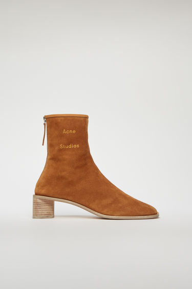 Acne Studios antique brown/ecru boots are crafted to a slim silhouette from supple suede and set on a stacked block heel. They are accented with a metal zip and a gold-stamped logo on the ankle.