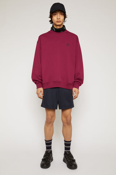 Acne Studios dark pink sweatshirt is crafted from midweight loopback jersey to an oversized silhouette with dropped shoulders and accented with a tonal face-embroidered patch on the chest.