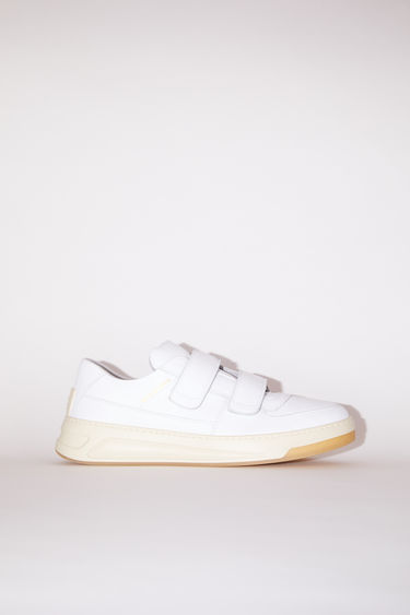 Acne Studios white velcro strap sneakers are made of calf leather with a round toe and a face motif on the back sole.