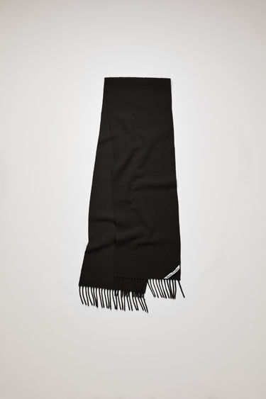 Acne Studios black scarf is crafted from soft wool that's pilled on one side and finished with fringed ends and a logo label across one corner.