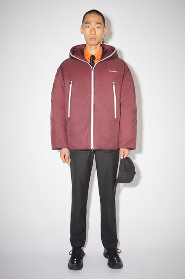 Acne Studios burgundy hooded down jacket is made of nylon with a quilted interior and Acne Studios branding at the chest.