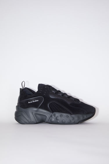Acne Studios black/black suede lace-up sneakers have organic, graphic soles.