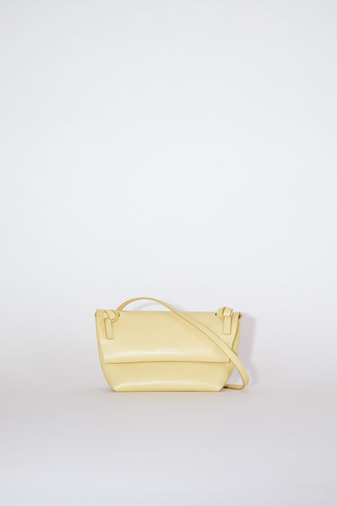 Acne Studios vanilla yellow flap purse features twisted knots inspired by traditional Japanese obi sashes.