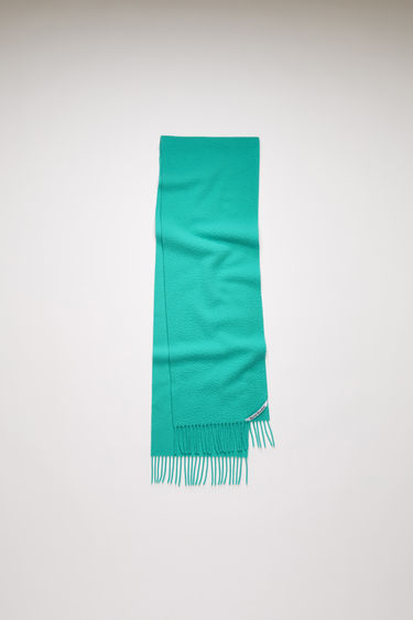 Acne Studios turquoise blue scarf is crafted from soft wool that's brushed on one side and features a logo label above the fringed edges.